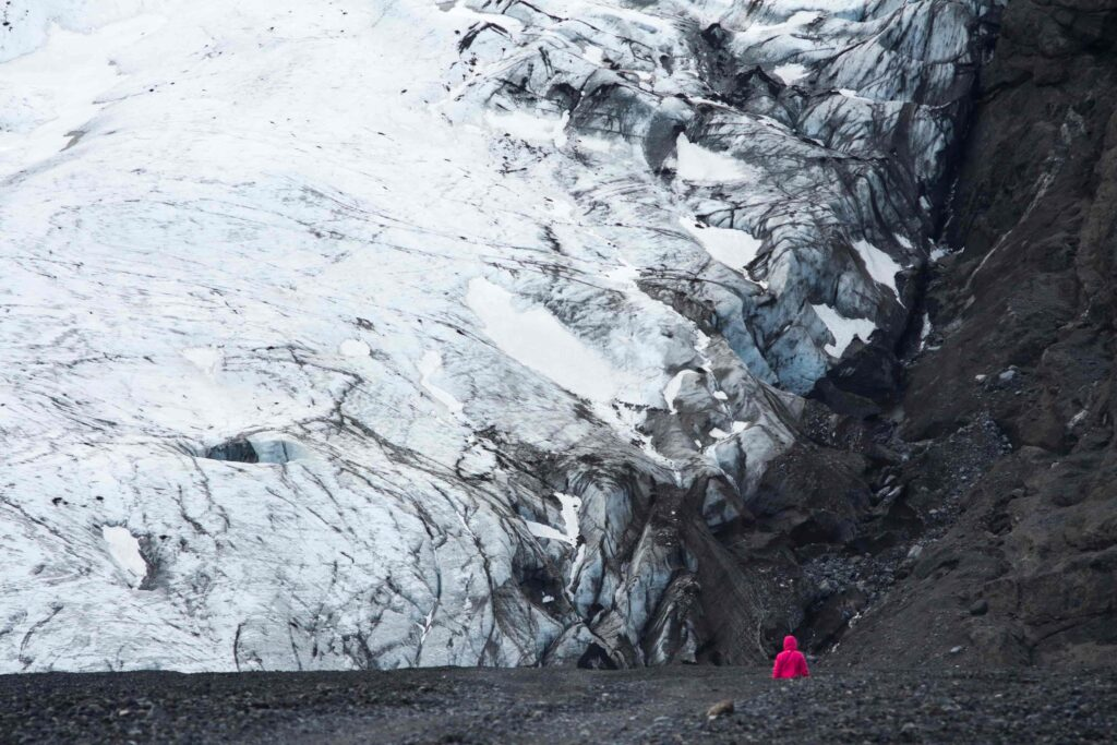 woman standing in front of Gígjökull glacier on the way to Thorsmork