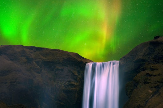 Northern lights at Skógafoss waterfall in Iceland