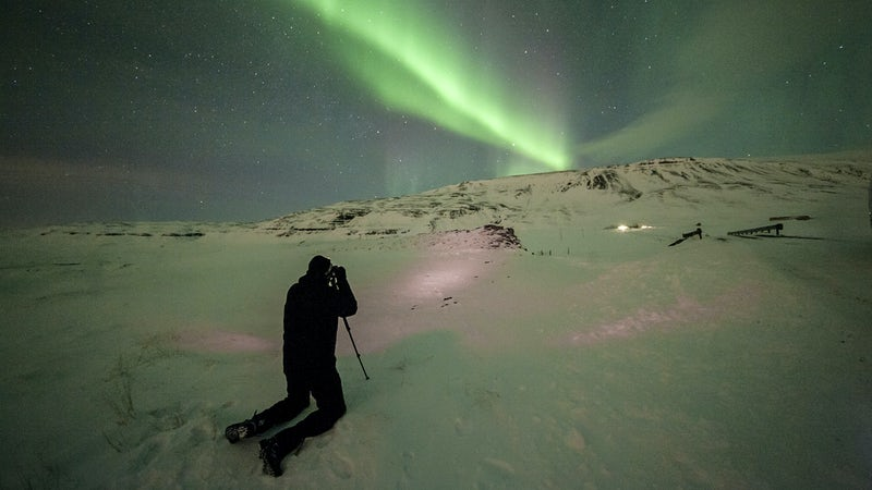 man taking a photo of the Northern lights in Iceland