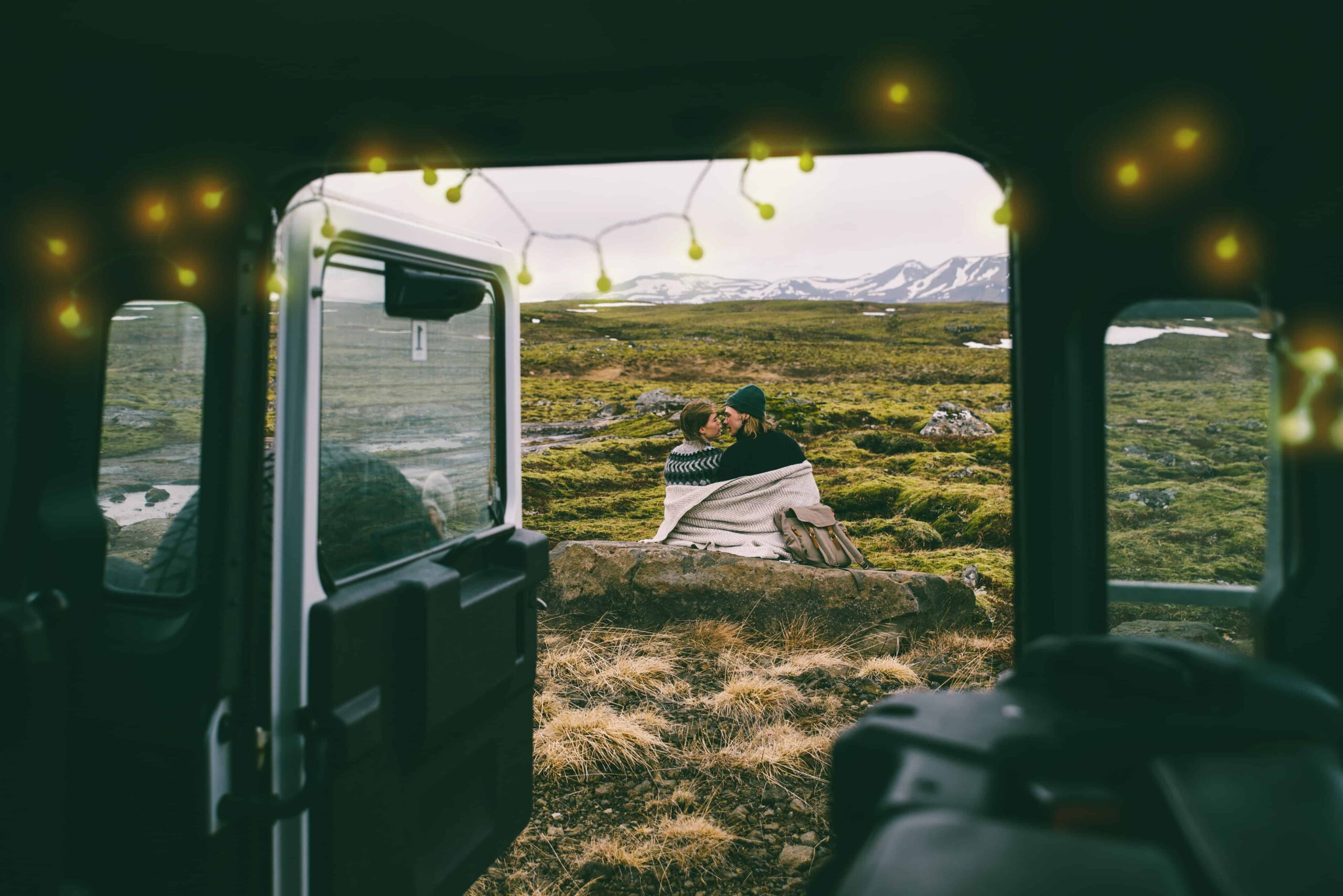 Two people in Icelandic wool sweater checking a map in a camper van in Iceland