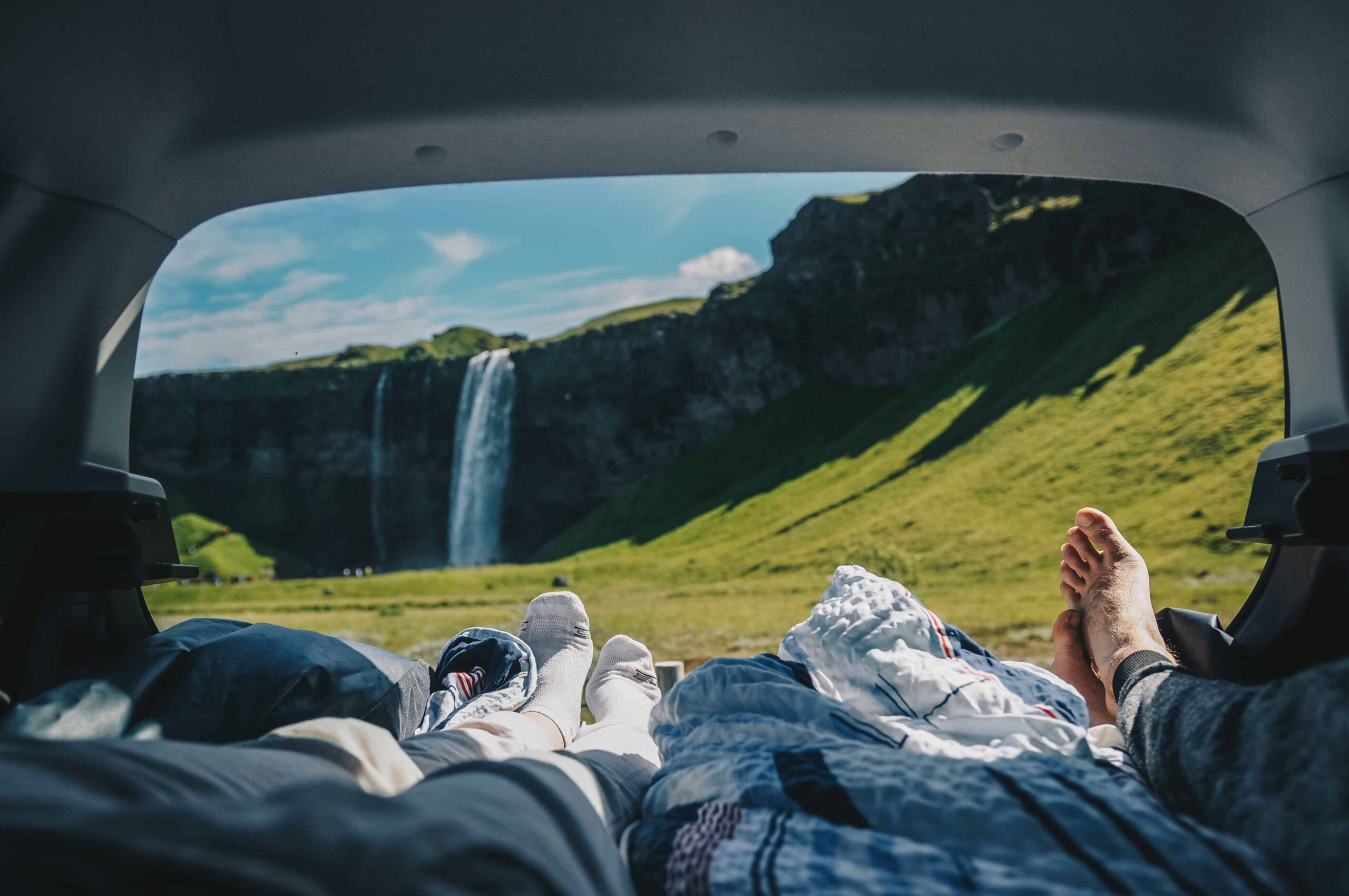 relaxing in the back of a camper van in front of Seljalandsfoss waterfall in South Iceland