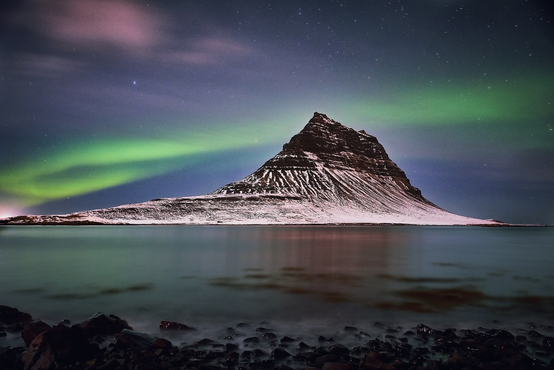 northern lights aurora borealis dancing over Kirkjufell mountain and Kirkjufellsfoss waterfall in Snæfellsnes Peninsula