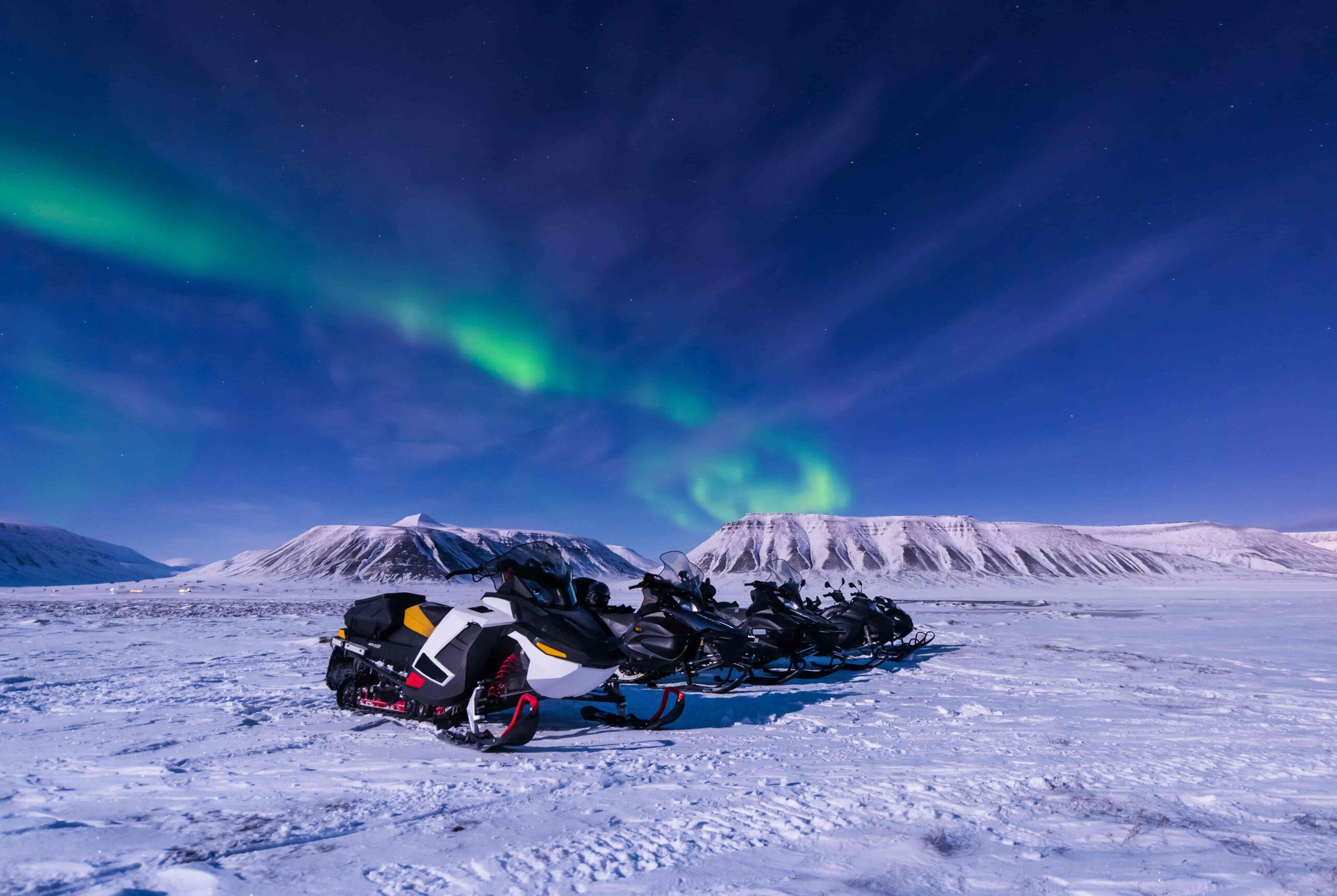 northern lights over snowmobiles in Iceland