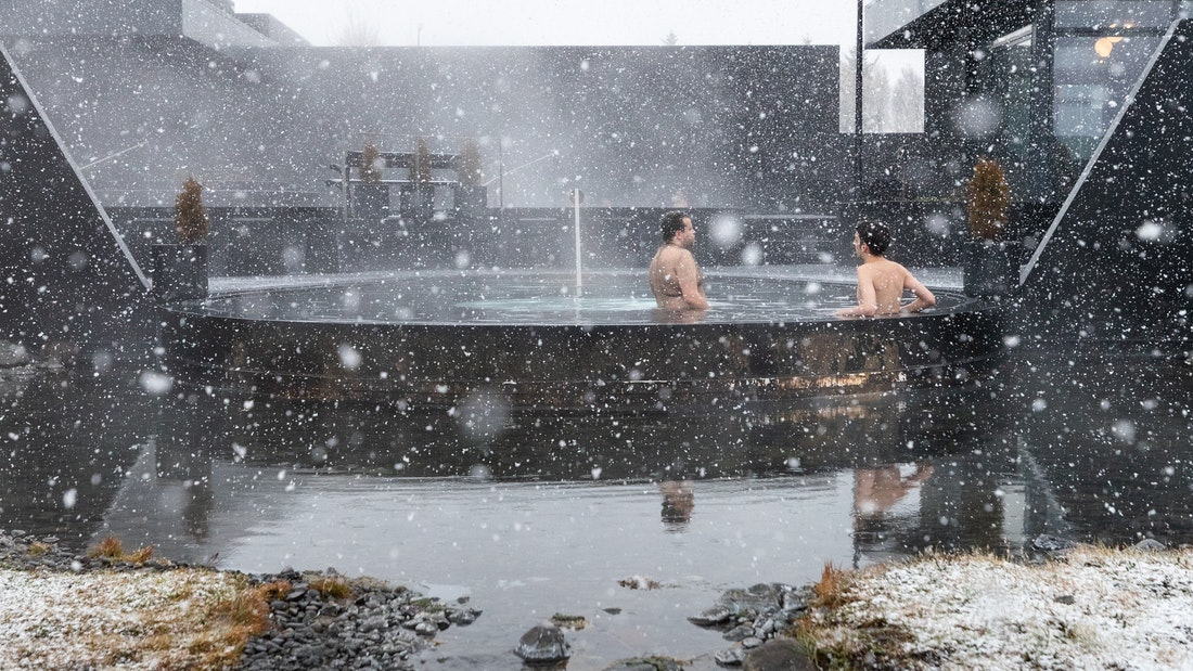 snow falling on two people at Krauma geothermal baths and spa in west Iceland during winter