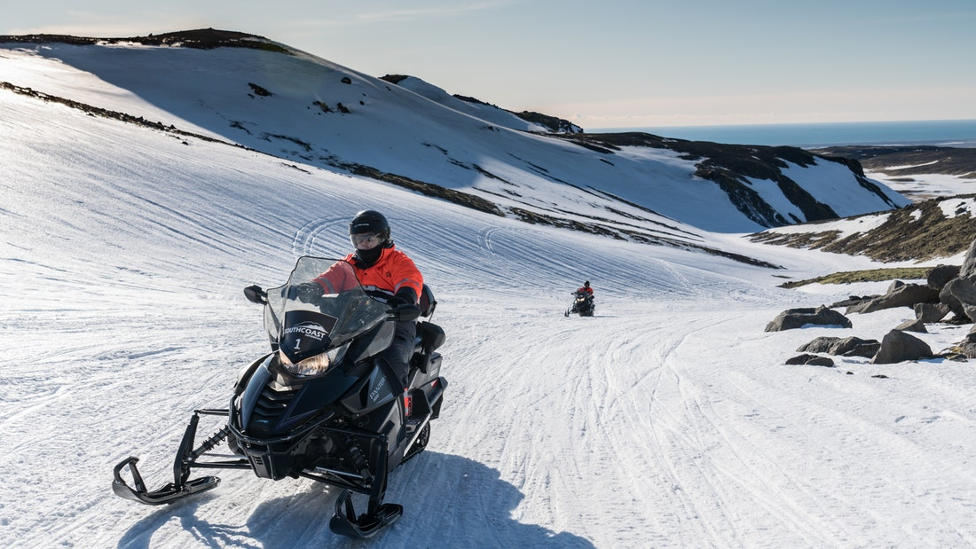 people riding a snowmobile on Eyjafjallajokull snowmobile tour in south Iceland