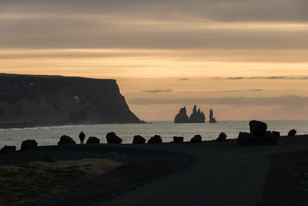 Kirkjufjara black sand beach and Eagle Rock in south Iceland with views over to Reynisfjara and Reynisdrangar