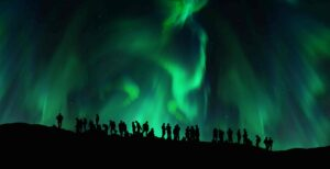 a group of people watching the northern lights in Iceland