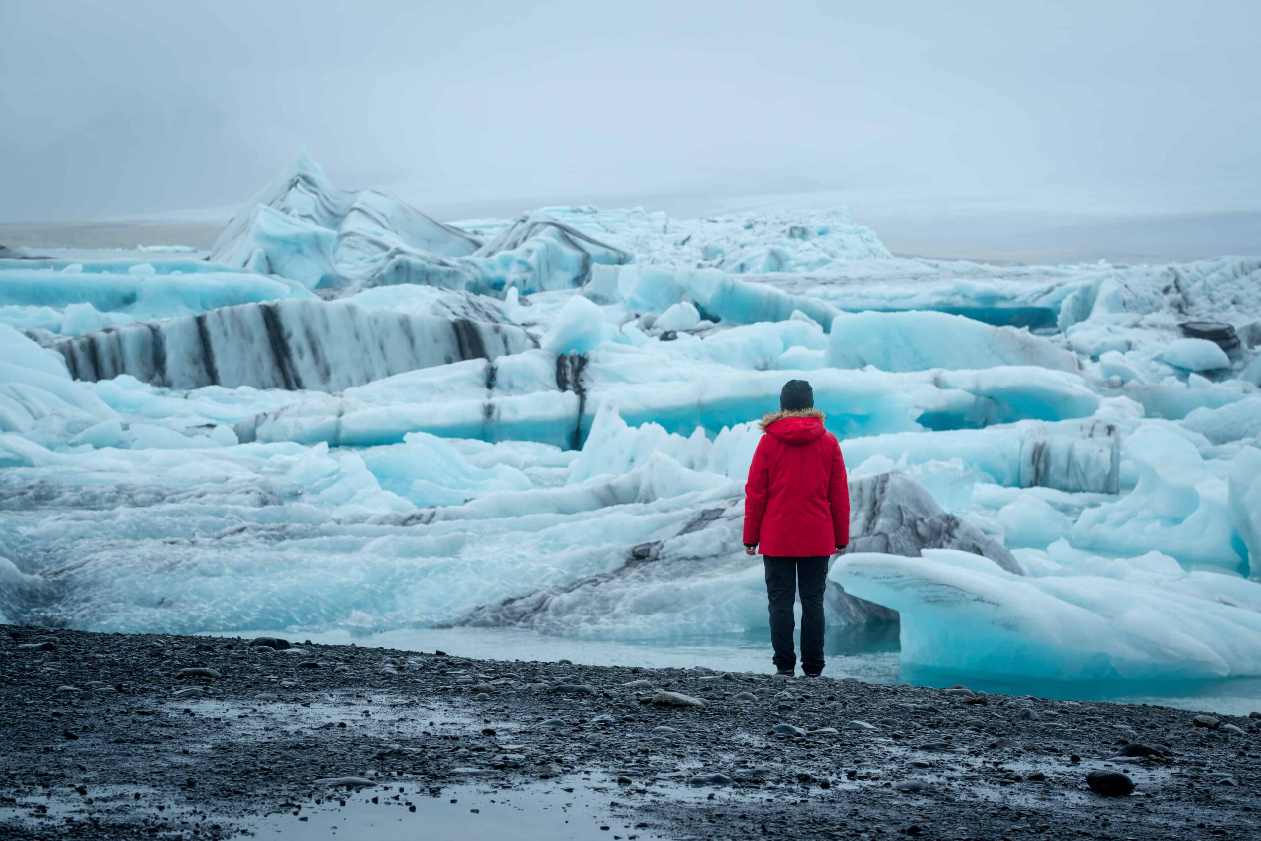 woman in red coat next to Jokulsarlon glacier lagoon in south Iceland