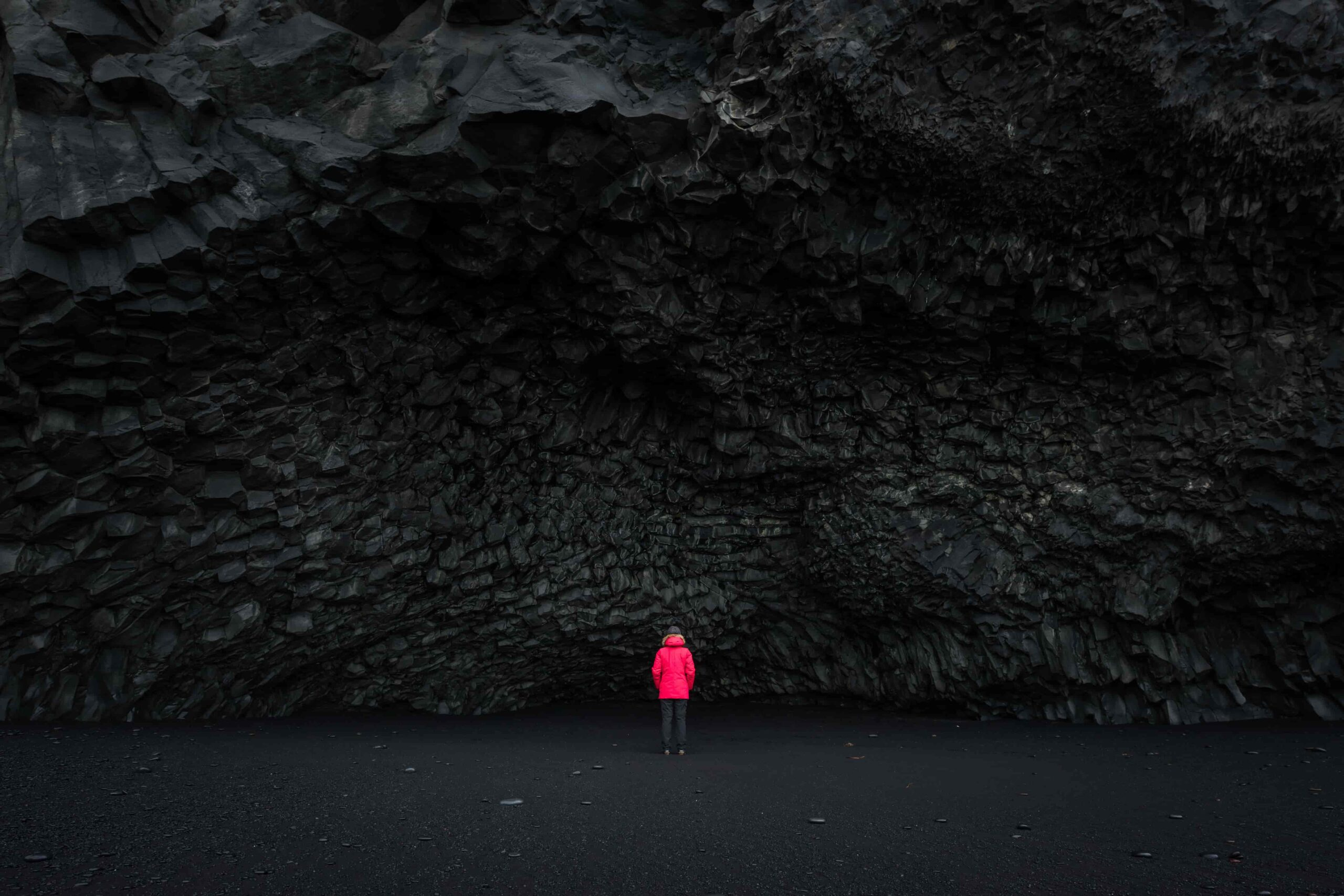 woman in red coat next to the cave at Reynisfjara black sand beach in south Iceland