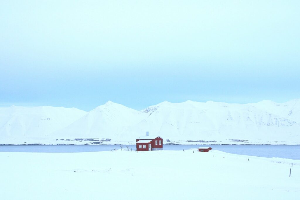 red house standing alone in the snow in Dalvík village in north Iceland