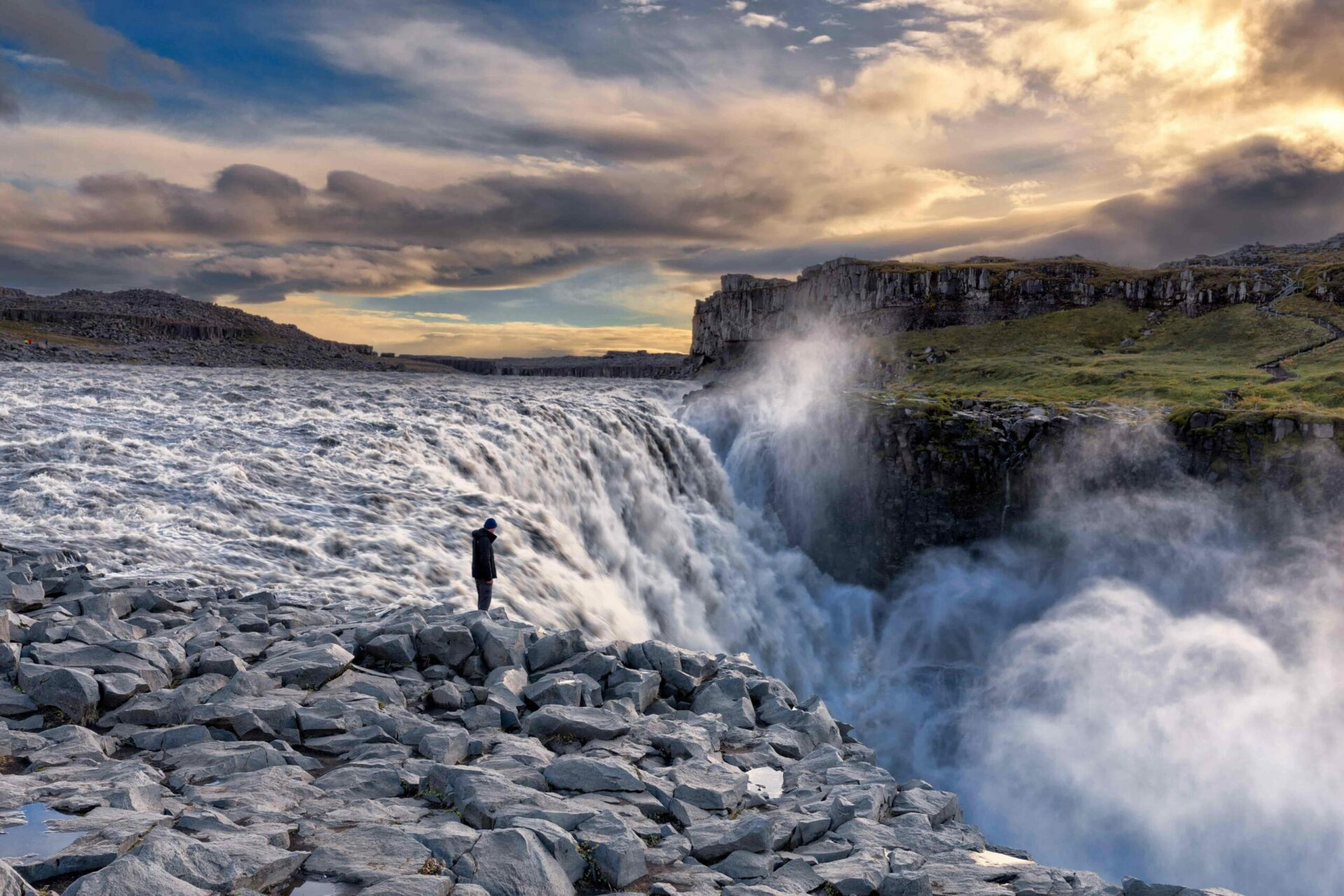 man standing in front of Dettifoss the most powerful waterfall in Europe