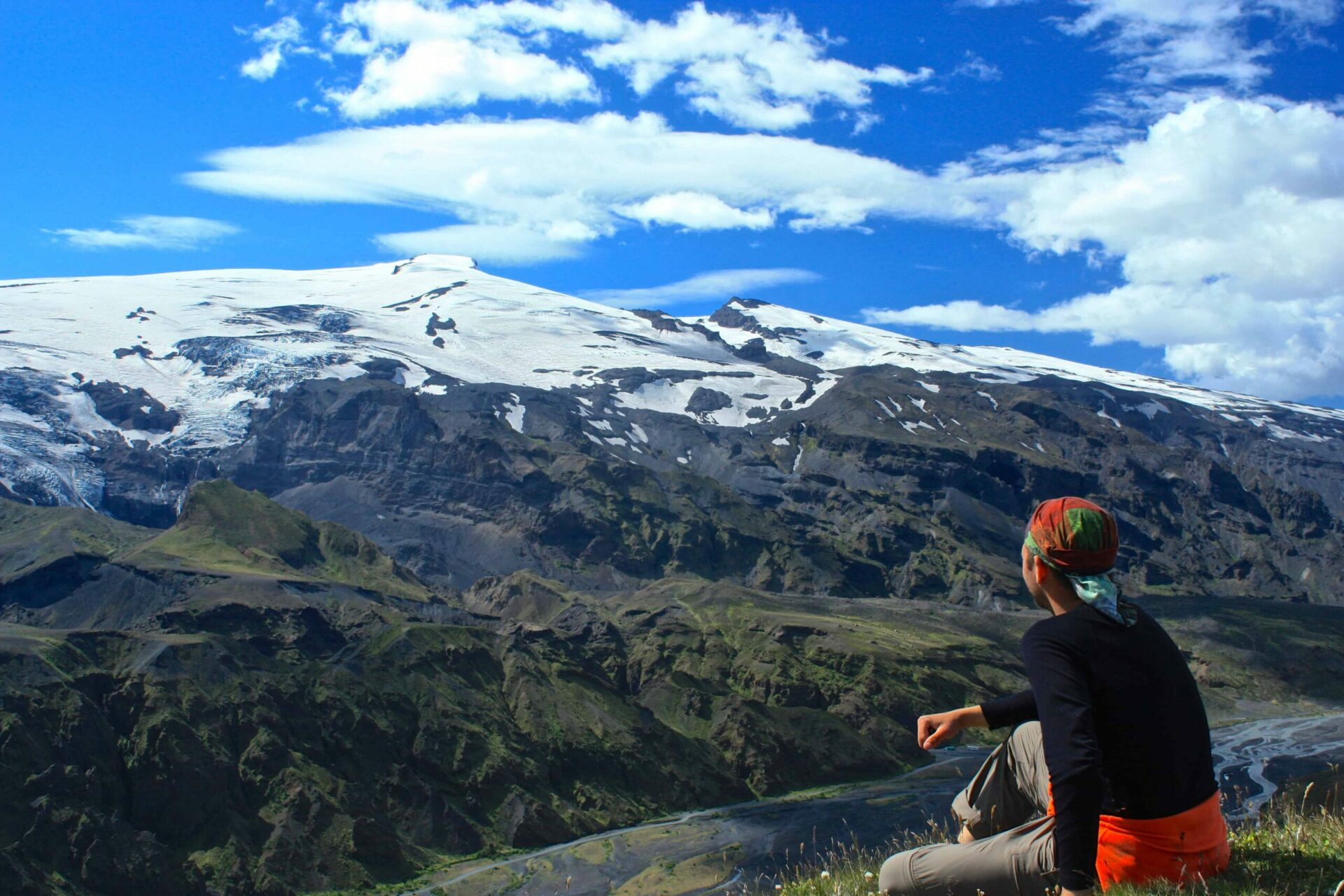 man sitting with a view over Eyjafjallajokull volcano and mountain in Iceland
