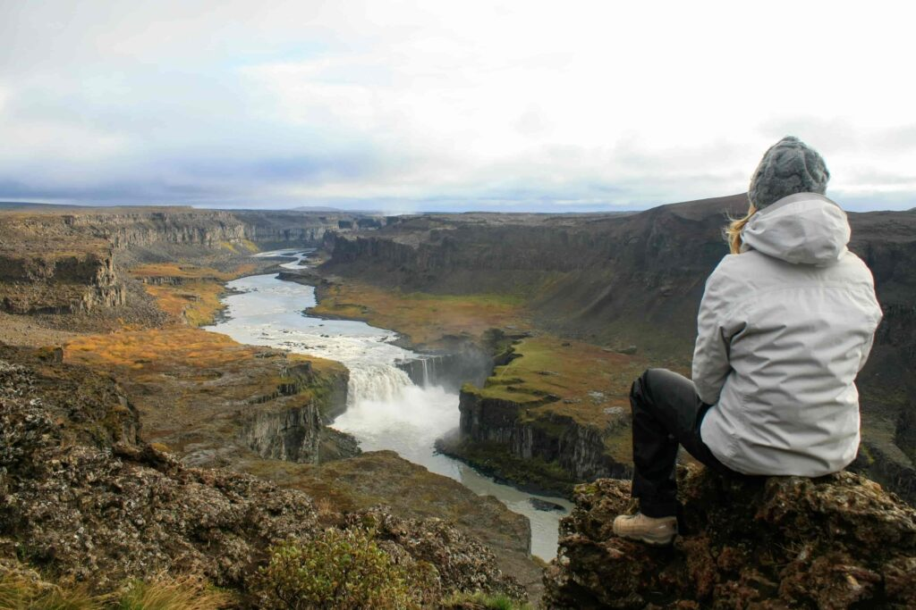 woman sitting at the viewpoint at Hafragilsfoss waterfall in the diamond circle in north Iceland
