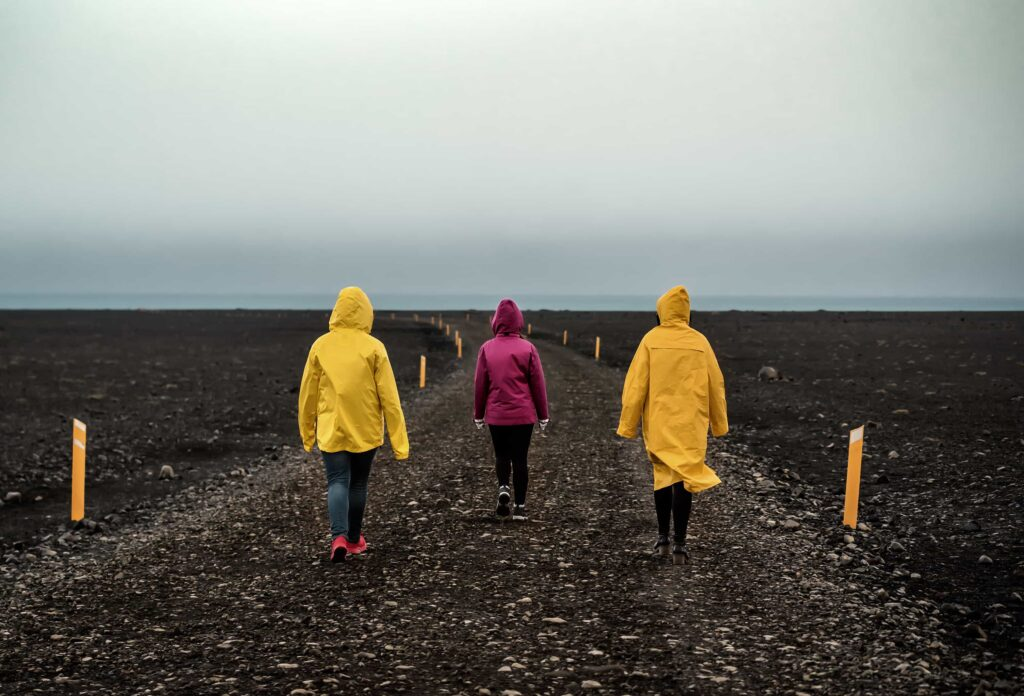 three people in yellow raincoats walking the black sand beach to Solheimasandur Plane Wreck in south Iceland