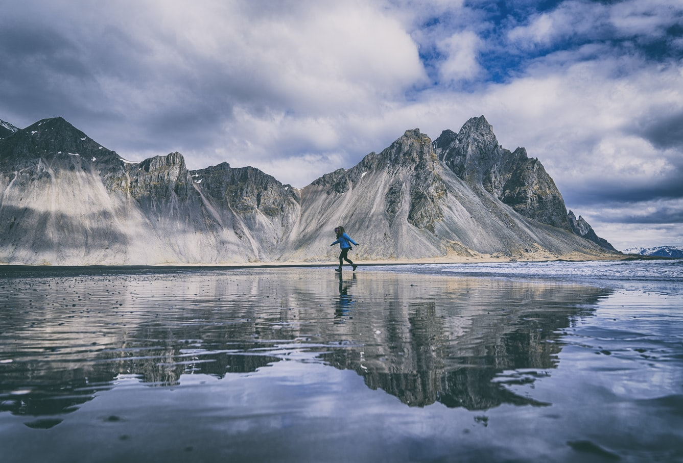 woman walking on the mirror beach at Vestrahorn and Stokksnes in south east Iceland