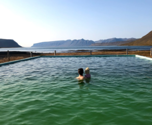 father and daughter looking at the amazing views from Reykjafjarðarlaug swimming pool in the westfjords of Iceland