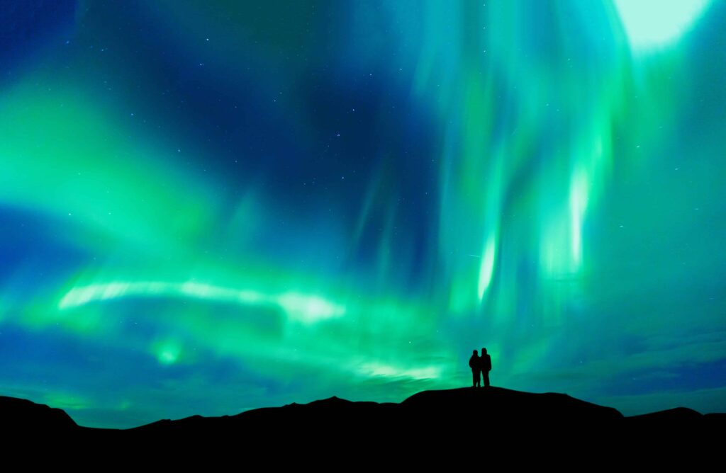 Honeymoon in Iceland, two people watching the northern lights in Iceland