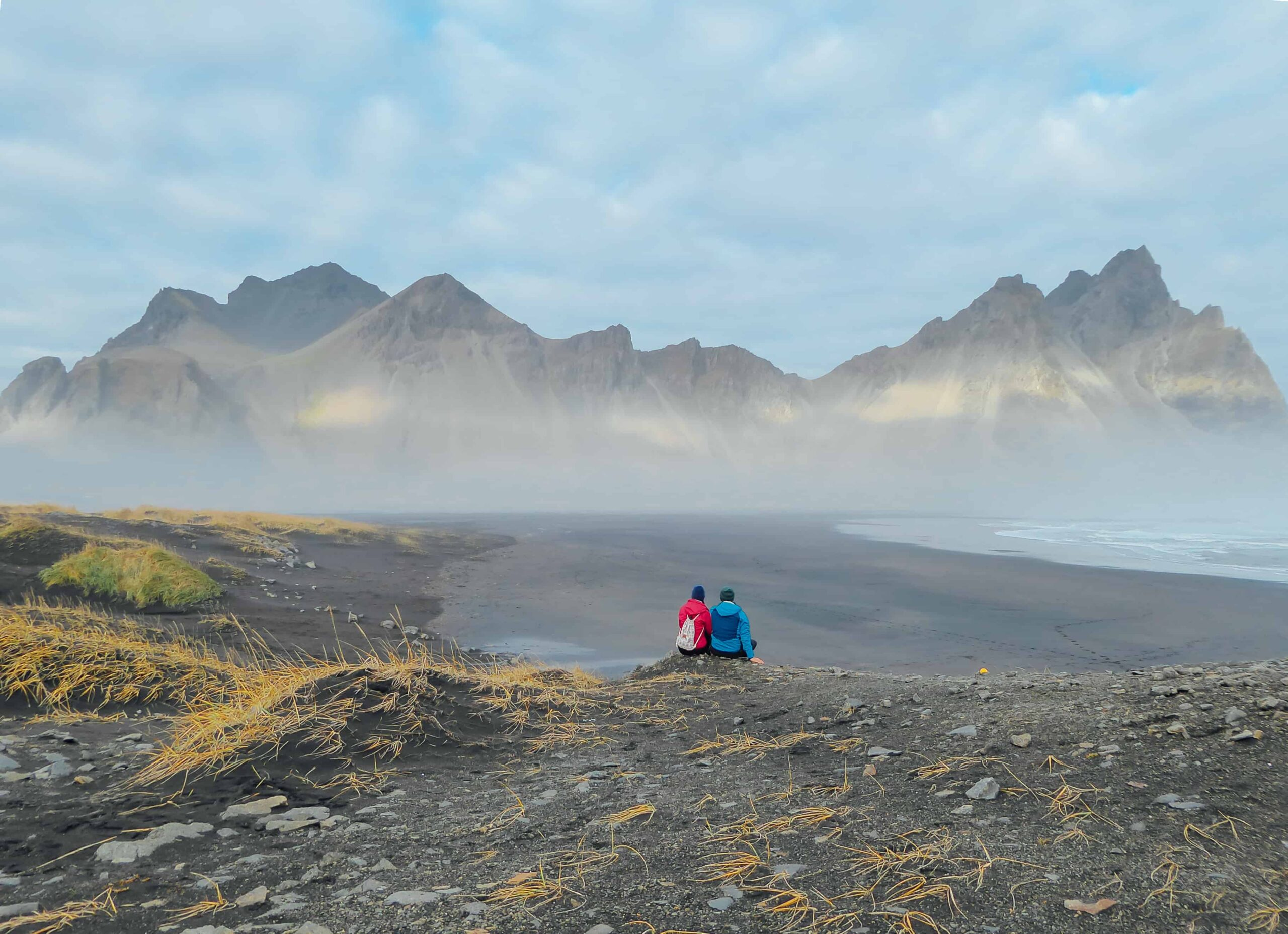 Honeymoon in Iceland, two people sitting in front of Stokksnes in east Iceland