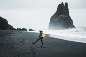 man with a Daypack in Iceland at Reynisfjara black sand beach