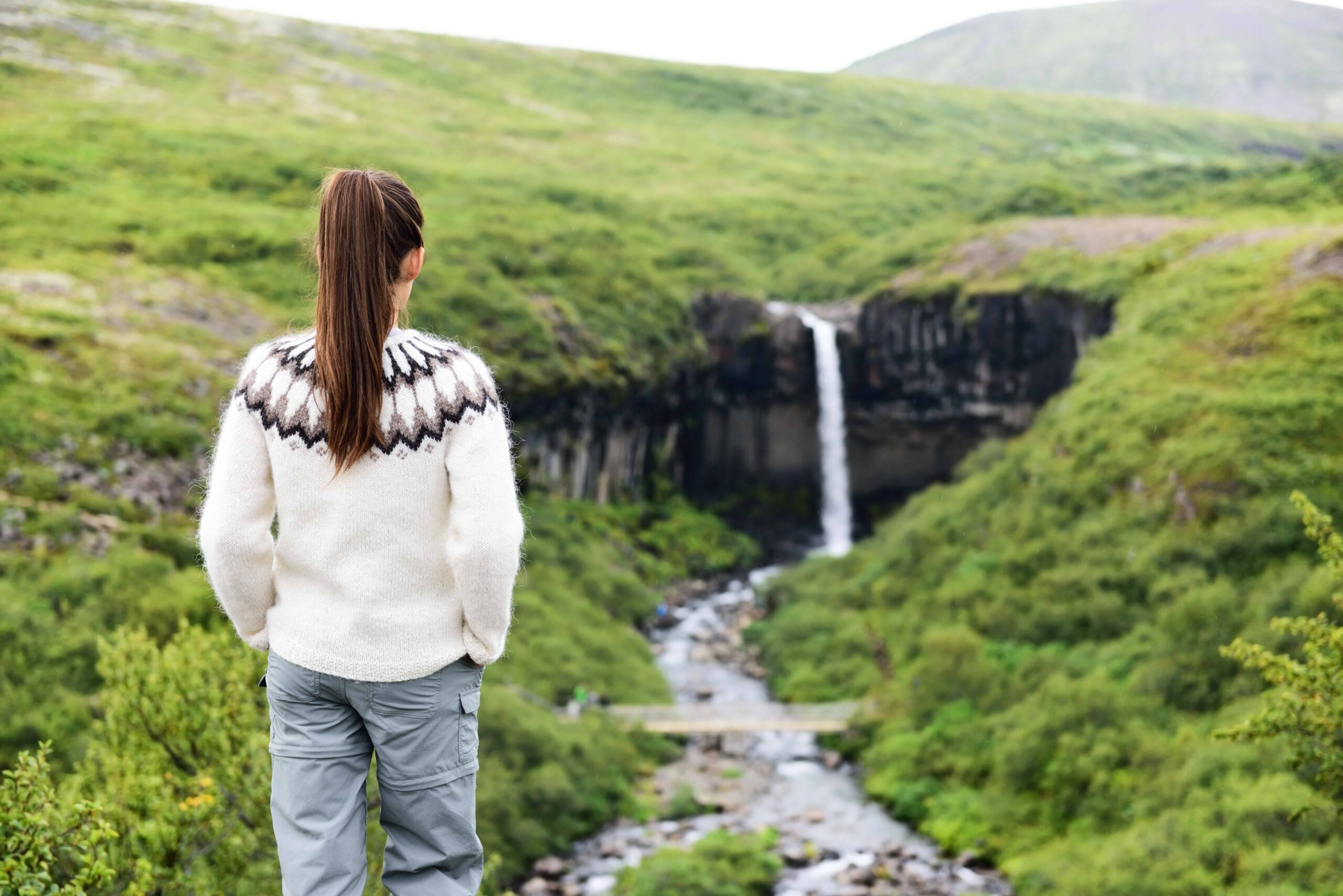 woman standing in an Icelandic wool sweater in front of Svartifoss waterfall in Skaftafell National Park