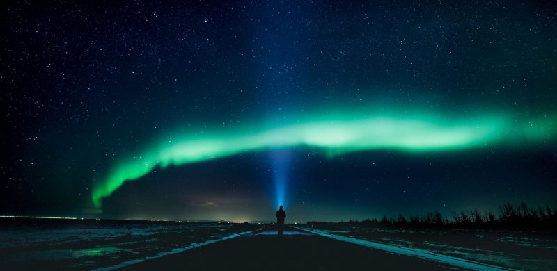 man watching the northern lights and stars in Iceland