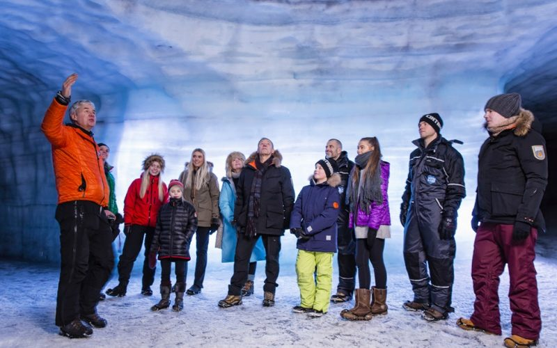 a group of people visiting into the glacier ice cave in Langjokull