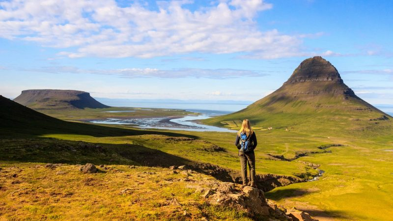 Hiking with a backpack next to Kirkjufell mountain in Iceland