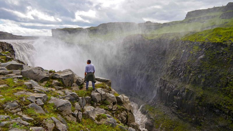 Man standing in front of Dettifoss waterfall the most powerful waterfall in Europe