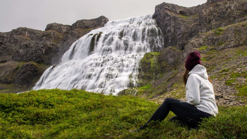 woman sitting in front of Dynjandi waterfall in the Westfjords