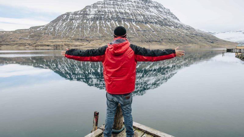 man standing in front of Hólmanes Mountin in Eskifjörður village in the Eastfjords of Iceland
