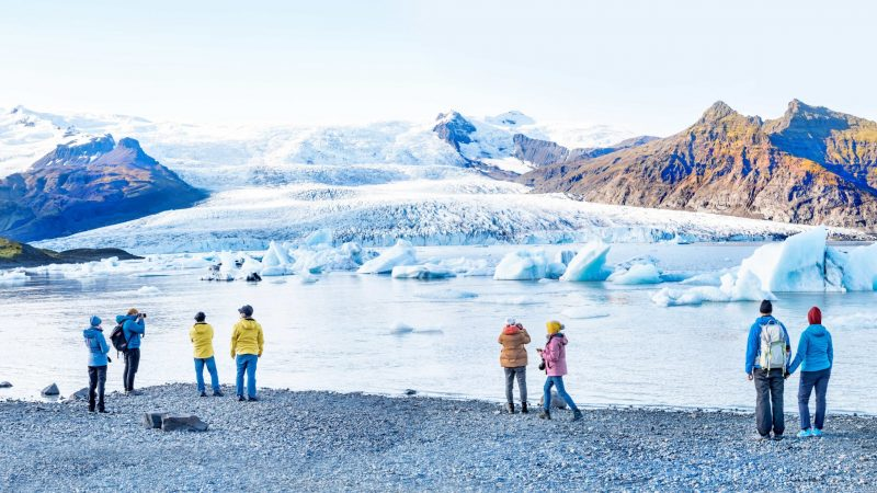 people standing in front of Fjallsárlón glacier lagoon in south Iceland