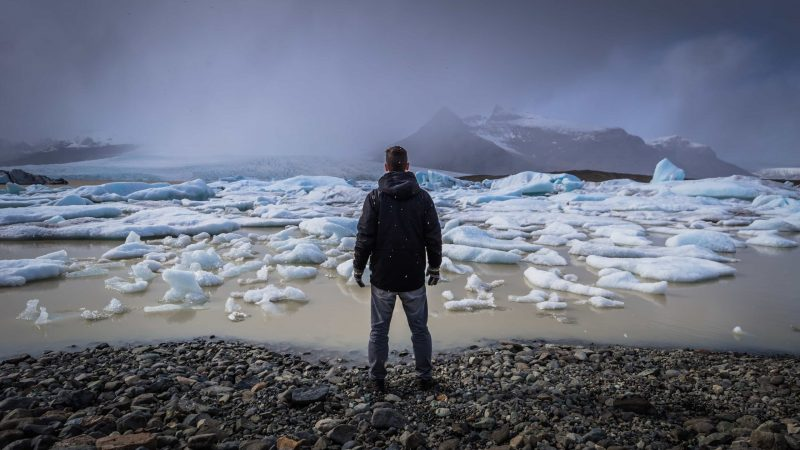 man standing in front of Fjallsárlón glacier lagoon in south Iceland