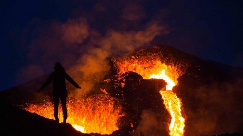 active volcano tour, man standing in front of Geldingadalur erupting volcano in Iceland