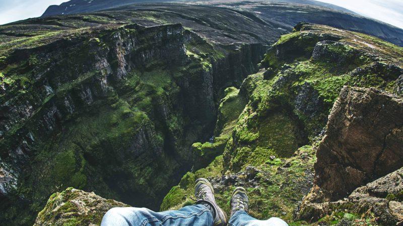 man sitting at Glymur highest waterfall in Iceland