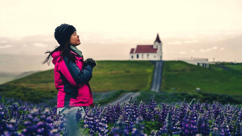woman standing in front of Hellissandur church and Snæfellsjokull glacier in Snæfellsnes Peninsula