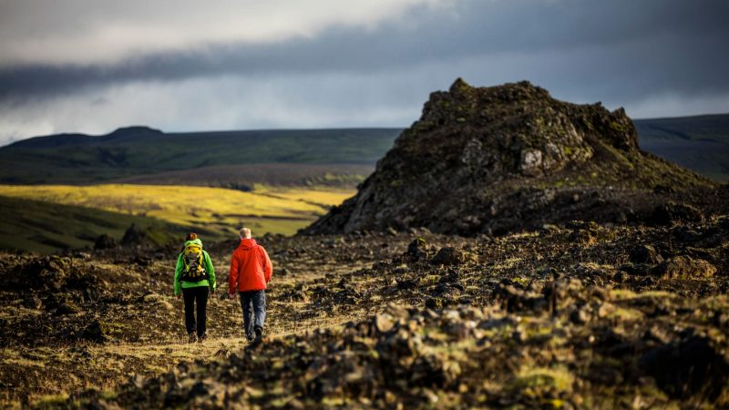 two people walking over lava fields in the highlands of Iceland