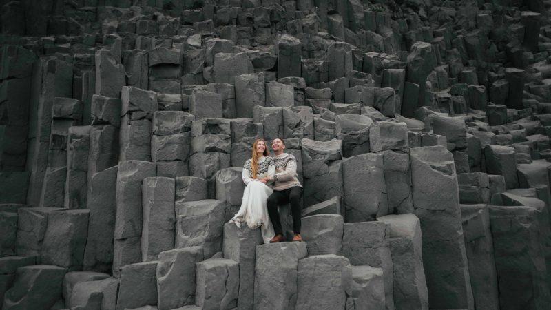 two people sitting in the basalt columns at Reynisfjara black sand beach, Honeymoon in Iceland
