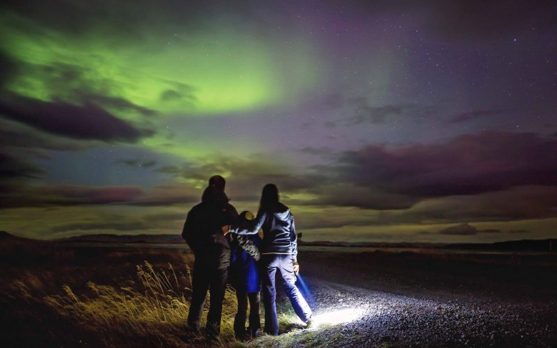 Family watching the northern lights in Iceland