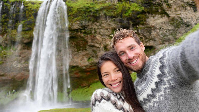 Honeymoon in Iceland, couple in front of Seljalandsfoss waterfall