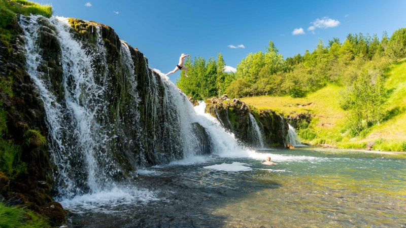 Iceland Family Travel, jumping into a waterfall in Iceland