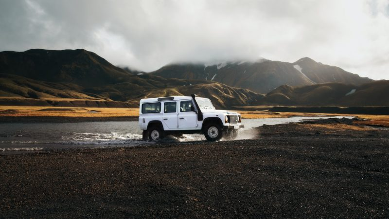 white jeep driving over a river in Iceland