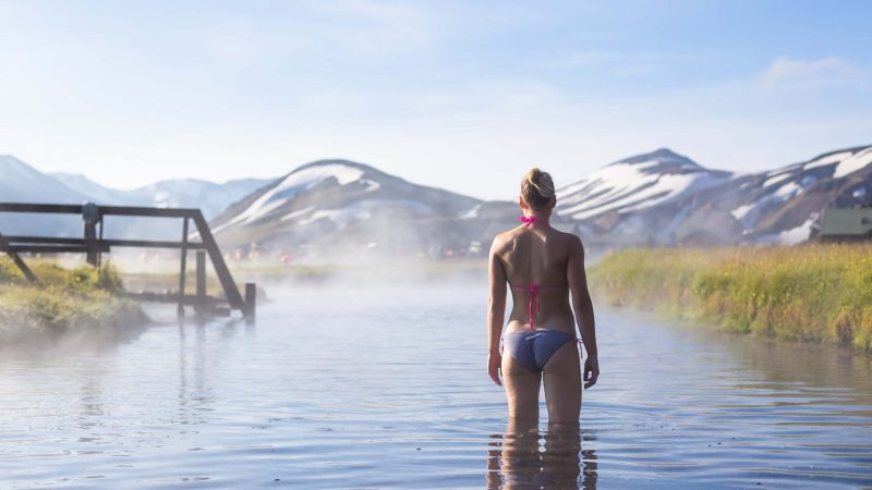 woman bathing in Landmannalaugar hot spring in the highlands of Iceland