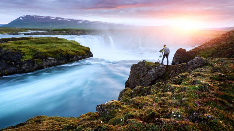 Photography in Iceland - man capturing Goðafoss waterfall on a photo