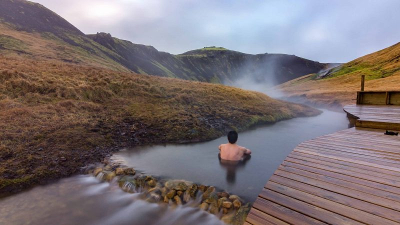 man sitting in Reykjadalur hot spring on the Reykjadalur hot spring and hike