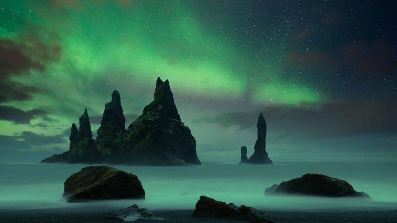 northern lights above Reynisdrangar on Reynisfjara black sand beach in south Iceland