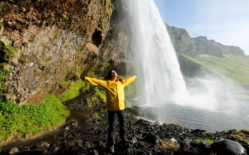 woman in yellow raincoat standing at Seljalandsfoss walk behind waterfall in south Iceland
