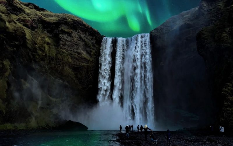 northern lights over Skogafoss waterfall