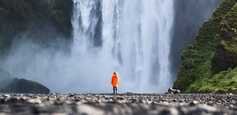 man standing in front of Skógafoss waterfall in south Iceland