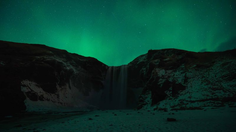 northern lights at Skógafoss waterfall in south Iceland