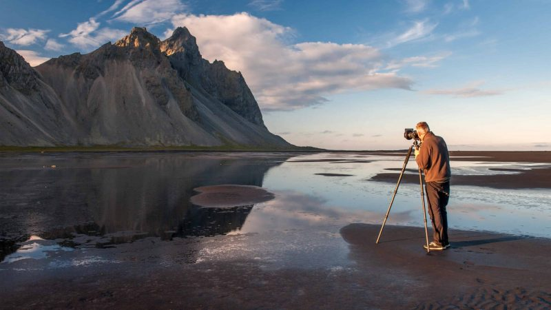 Man photographing Vestrahorn mountain from Stokksnes black sand beach in south east Iceland